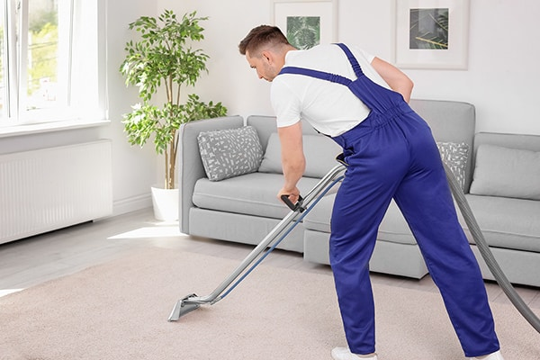 technician cleaning a rug with steam wand