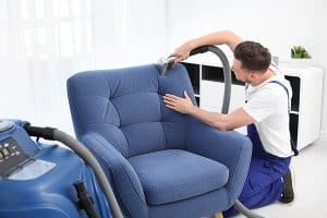 technician cleaning a blue fabric armchair